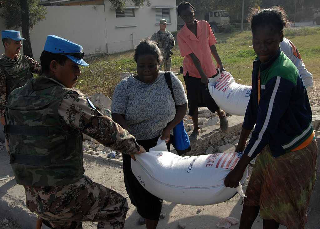 1024px-A_United_Nations_peacekeeper_from_Jordan_assists_a_Haitian_woman_carrying_a_100-pound_bag_of_rice_outside_Port-au-Prince,_Haiti_100213-N-HX866-003