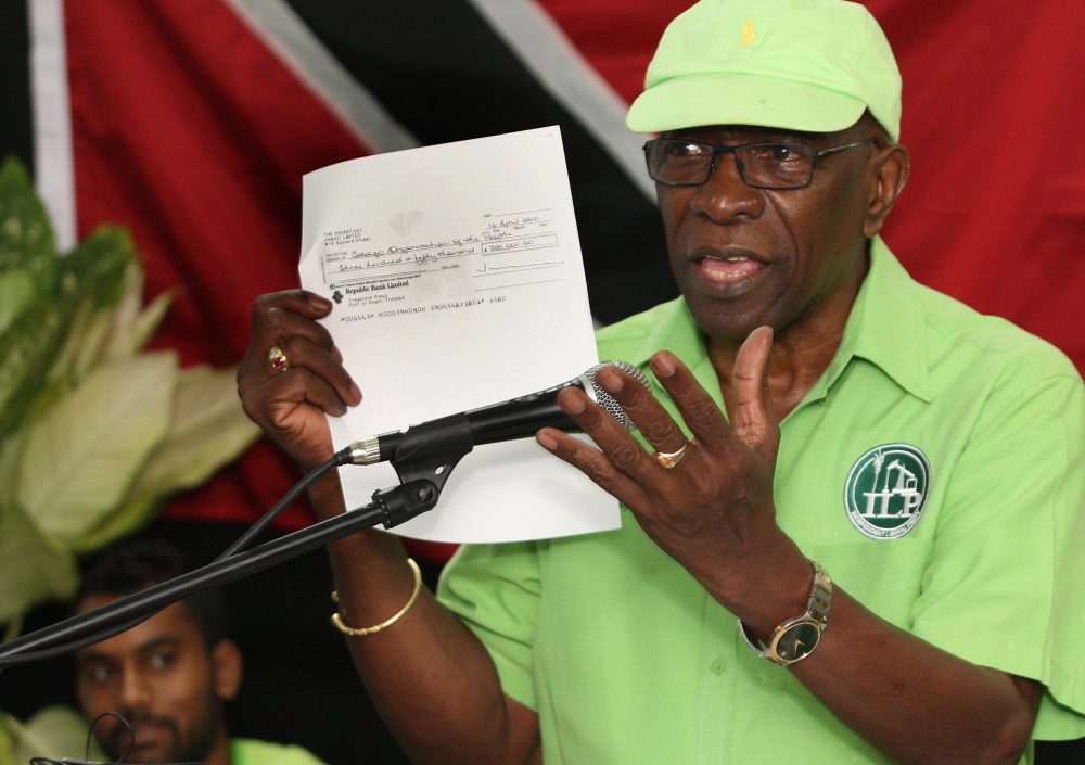 Former FIFA vice president Jack Warner hold a copy of a check while he speaks at a political rally in Marabella, Trinidad and Tobago, Wednesday, June 3, 2015. Warner made a televised address Wednesday night, saying he will prove a link between soccer's governing body and his nation's elections in 2010. Warner said he has documents and checks that link FIFA officials, including embattled President Sepp Blatter, to the 2010 election in Trinidad and Tobago. (Photo/Anthony Harris) ORG XMIT: XAH102